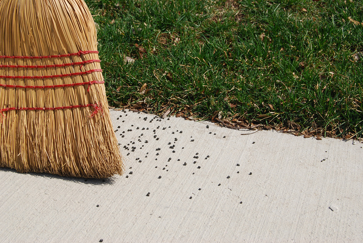 Sweeping excess fertilizer off hard surfaces